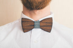 Fashion style. Bearded man in a shirt with a wooden bow tie stock photo