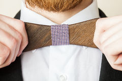 Fashion style. Bearded man in a shirt with a wooden bow tie royalty free stock images