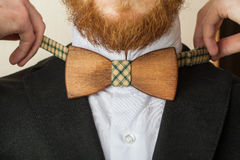 Fashion style. Bearded man in a shirt with a wooden bow tie stock image