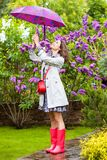 Fashion, style. Beautiful woman with umbrella in the rain blossom garden stock images