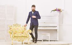 Fashion and style concept. Macho attractive and elegant on serious, thoughtful face standing near old fashioned armchair. Man with beard and mustache wearing royalty free stock photo