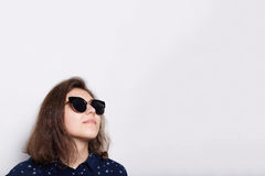 Fashion and style concept. A stylish elegant young brunette wearing sunglasses looking up isolated over white background. Portrait Stock Image