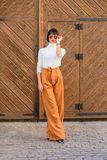 Fashion and style concept. Woman walk in loose pants. Woman fashionable brunette stand outdoors wooden background. Girl. With makeup posing in fashionable stock photography