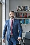 Fashion, style, dress code. Man with beard in blue formal suit. Business, entrepreneurship concept. Businessman or director pose at workplace. Career Stock Image