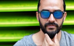 Close up of man in sunglasses touching beard Royalty Free Stock Photography