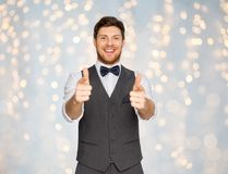 Happy man in festive suit pointing in camera. Fashion, style and gesture concept - happy man in festive suit pointing fingers in camera over holidays lights Stock Photography