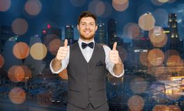 Happy man  showing thumbs up over singapore city. Fashion, style and gesture concept - happy man in festive suit showing thumbs up over singapore city night Royalty Free Stock Photos