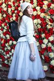 Fashion style. Girl dressed stylishly.Girl in a lush skirt. Wall in red and white roses Stock Photos