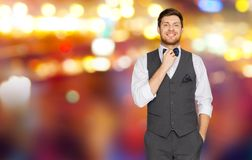 Man in festive suit over night city lights. Fashion, style and holidays concept - happy man in festive suit dressing for party and adjusting bowtie over night Stock Images