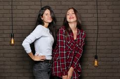 Two young and beautiful womans are posing near the brick wall Stock Photos