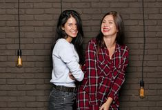 Two young and beautiful womans are posing near the brick wall Stock Photography