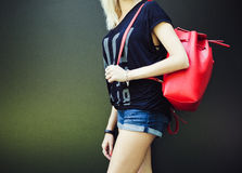 Fashion and Style. trendy red backpack over his shoulder at the girl. part of the body on a dark background Royalty Free Stock Images