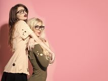 Fashion, style, vogue. Women with long hair in geek glasses. Visage, makeup, hairstyle. Girls pose in torn clothes on pink background. Beauty, look concept Stock Photos