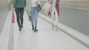 Fashion styled girl friends marching at the mall with shopping bags in their hands -. Fashion styled girl friends marching at the mall with shopping bags in stock footage