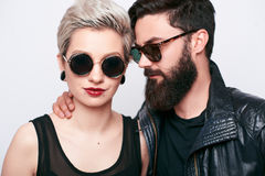 Fashion stylish bearded young man and blond woman. Closeup portrait of bearded young men and blond women wearing sunglasses. Stylish couple in biker vintage royalty free stock photos