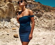 Model in summer blue dress posing near sand rocks Stock Images