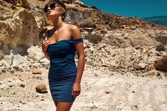 Model in summer blue dress posing near sand rocks Stock Photos