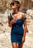 Model in summer blue dress posing near sand rocks Stock Image