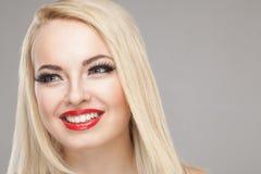 Fashion Stylish Beauty portrait of smiling beautiful blonde girl. With professional make-up, false eyelashes and red lips on white background Stock Photography