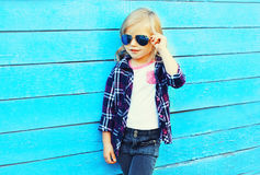 Fashion stylish child wearing a sunglasses and checkered shirt. On a blue background, profile view royalty free stock photography