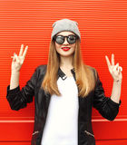 Fashion stylish cool girl having fun wearing a rock black leather jacket and sunglasses with hat Stock Photography