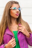 Fashion stylish girl in sunglasses and a bright pink jacket stock photography