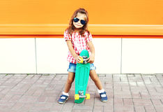 Fashion stylish little girl child with skateboard wearing sunglasses and checkered shirt in city Stock Photos