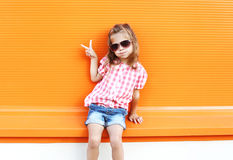 Fashion stylish little girl child wearing sunglasses and checkered shirt having fun in city Royalty Free Stock Photos