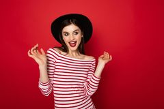 Coquettish girl in striped blouse and black hat royalty free stock photography
