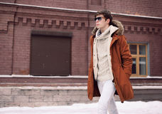 Fashion stylish man wearing a jacket and sunglasses walking Stock Photo
