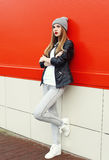 Fashion stylish pretty woman wearing a rock black leather jacket and hat over red Royalty Free Stock Photo