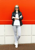 Fashion stylish pretty woman wearing a rock black leather jacket and sunglasses in city Royalty Free Stock Photos