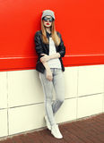 Fashion stylish pretty woman wearing a rock black leather jacket and sunglasses with hat Royalty Free Stock Image