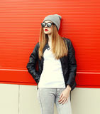 Fashion stylish woman wearing a rock black leather jacket and sunglasses with hat Stock Photo
