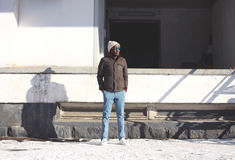 Fashion stylish young african man standing wearing a jacket with knitted hat, winter street style royalty free stock photography