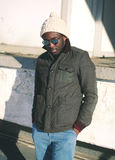 Fashion stylish young african man wearing a sunglasses and jacket with knitted hat Stock Photography