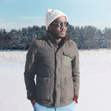Fashion stylish young african man wearing a sunglasses and jacket with knitted hat in winter. Day over snow Royalty Free Stock Image