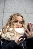 Fashion stylish young woman using smartphone in city Royalty Free Stock Photography