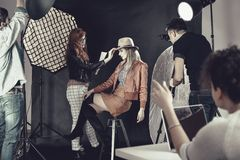 Fashion stylist with model at photoshoot Stock Photos