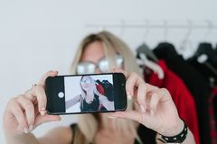 Fashion stylist selfie mobile influencer lifestyle. Fashion stylist taking selfie on mobile phone with fashionable clothes in background. social media influencer stock images