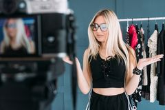 Fashion stylist vlog video streaming showroom. Fashion stylist vlogging. social media influencer creating content. video streaming. woman standing in clothing stock image