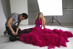 Fashion stylists adjusts model's footwear in studio royalty free stock photos