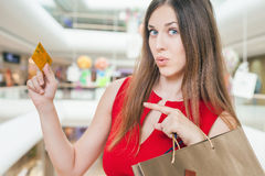 Fashion successful woman holding bags and pointing on credit card Stock Photography