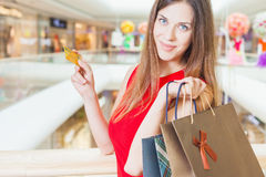 Fashion successful woman holding credit card and bags, shopping mall Royalty Free Stock Image