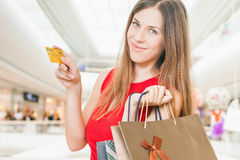Fashion successful woman holding credit card and bags, shopping mall Stock Photos