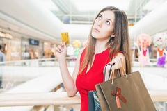 Fashion successful woman holding credit card and bags, shopping mall Royalty Free Stock Images