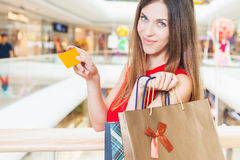 Fashion successful woman holding credit card and bags, shopping mall Stock Image