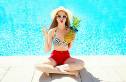 Fashion, summer holidays concept - woman with pineapple having fun on a blue water pool Royalty Free Stock Photos