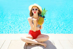 Fashion, summer holidays concept - woman with pineapple sends an air kiss Royalty Free Stock Photo