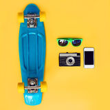 Fashion summer look concept. Blue skateboard, green sunglasses, vintage camera and screen smartphone on a yellow background. Top view. Trendy colorful photo Stock Photography
